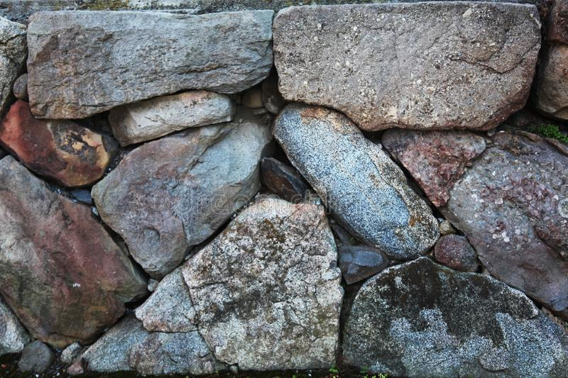 Stone wall with rough textures arranged together. Large stone wall in grey with rough textures arranged nicely together stock photography