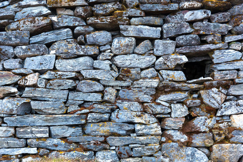 Stone Wall of rural Building made with manual work only. Stone Wall of rural Building made with manual work without linking solution of small pieces of rocks stock photos