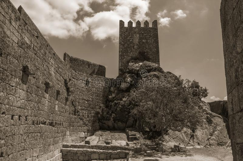Pathway over wall and tower from keep in a castle. Stone wall with square tower from keep in front of rocky courtyard at the Sortelha Castle. One of the most stock photo