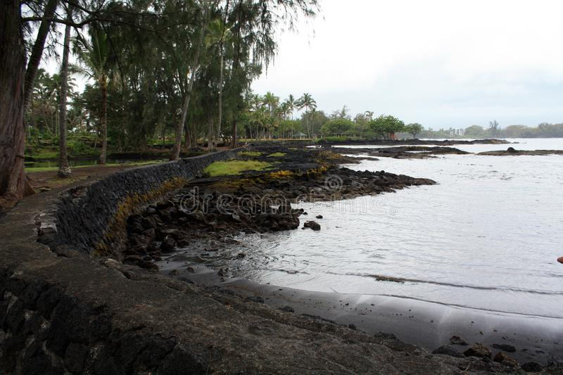 Horizontal photo of Stone wall on a Black sand beach in Hana Hawaii vertical fle. Stone wall surrounding shore line. Horizontal format Photograph. Wall  to royalty free stock images