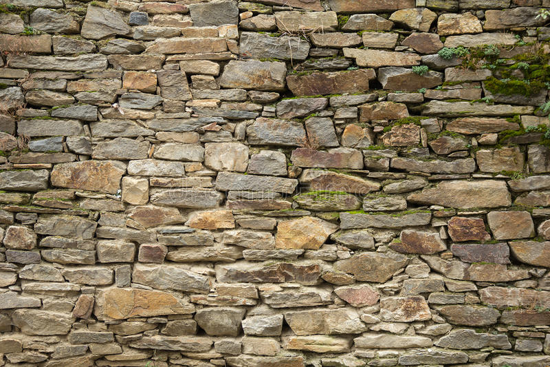 Stone wall texture. Old stone wall of natural stone oval royalty free stock photo