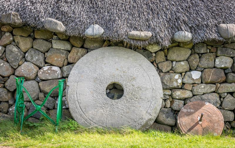 A stone wall with a thatched roof. a large stone millstone leaning on a wall royalty free stock photos