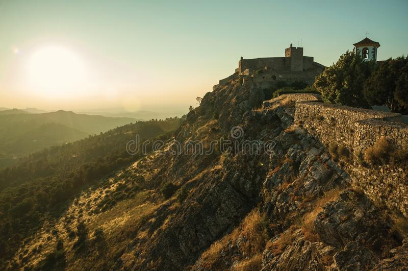 Stone wall and tower of Castle over ridge in Marvao. Stone wall and tower of Castle over cliff, with mountainous landscape covered by trees on sundown day at stock photo