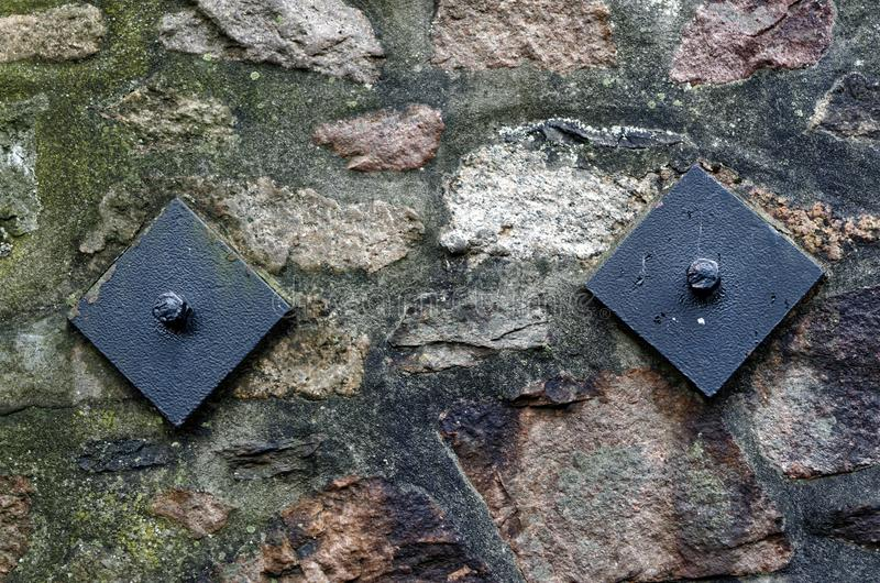 Stone wall with two black bolts. In so called Treppenviertel, Hamburg Blankenese, Germany royalty free stock images