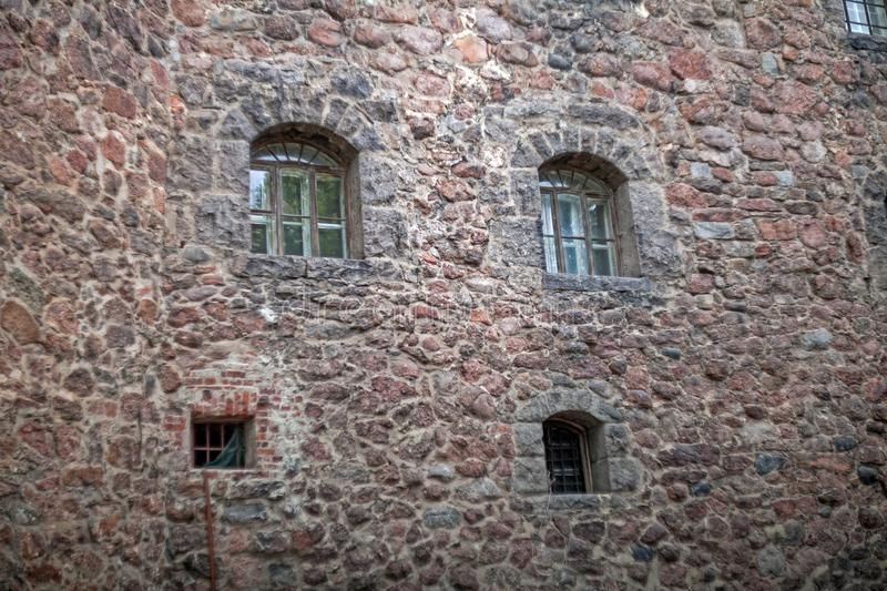 Stone wall with windows loopholes of an old Swedish castle in Vyborg. Russia stock photo