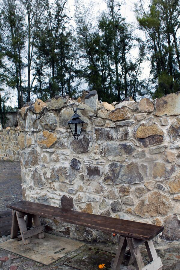 Stone wall and a wood bench. Looking quite vintage a cloudy day royalty free stock image