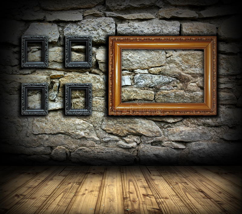 Stone wall with wood painting frames. Stone wall with old wood empty painting frames for interior design royalty free stock image