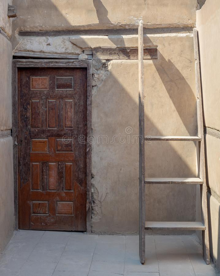 Stone wall with wooden grunge old decorated door and broken wooden ladder stock images