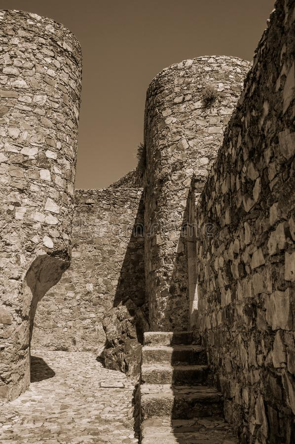 Stone walls and round tower at the Marvao Castle. Close-up of thick solid stone walls and round tower in a sunny day at the Marvao Castle. An amazing medieval stock image