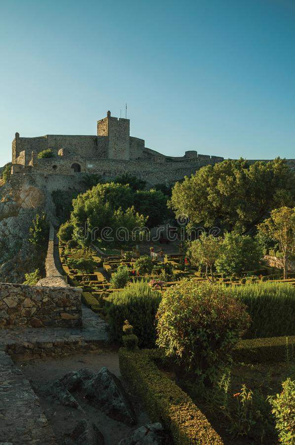 Stone walls and tower of Castle with lush flowered garden royalty free stock photo