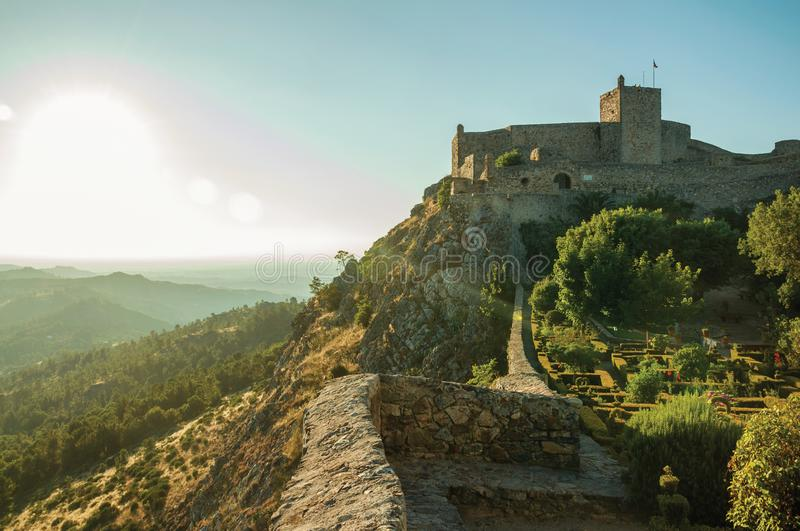 Stone walls and tower of Castle with lush flowered garden stock photography