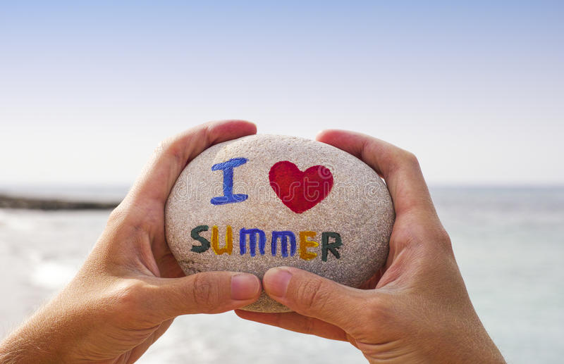 Stone with words I love summer in person hands stock image
