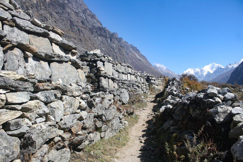 Stone aligned path upto kyanging gompa. Stoned aligned way in mountain region area of Nepal is a symbolic icon of Buddhism representing that it will bring royalty free illustration