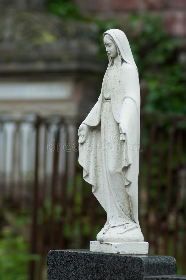 Stoned Virgin Mary. on tomb in cemetery. Closeup of stoned Virgin Mary. on tomb in cemetery stock photography