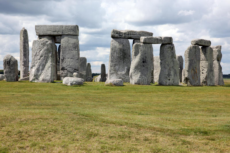 Stonehenge historic site on green grass under blue sky. Stonehenge is a UNESCO world heritage site in England with origins royalty free stock images