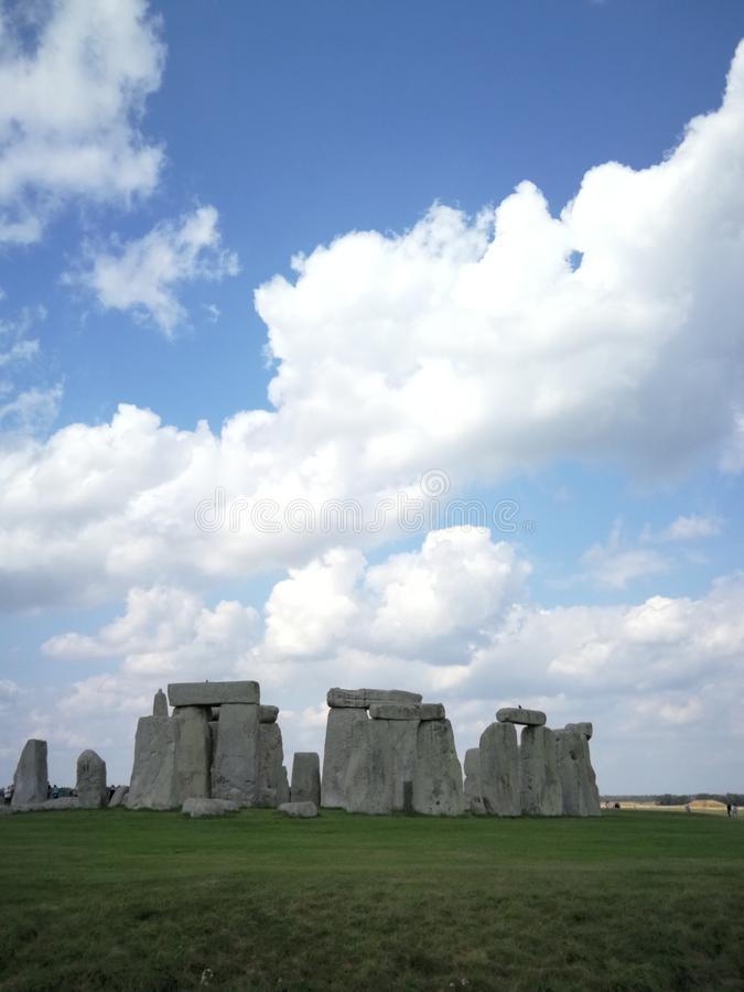 Stonehenge, Inghilterra sotto i cieli blu nuvolosi immagine stock