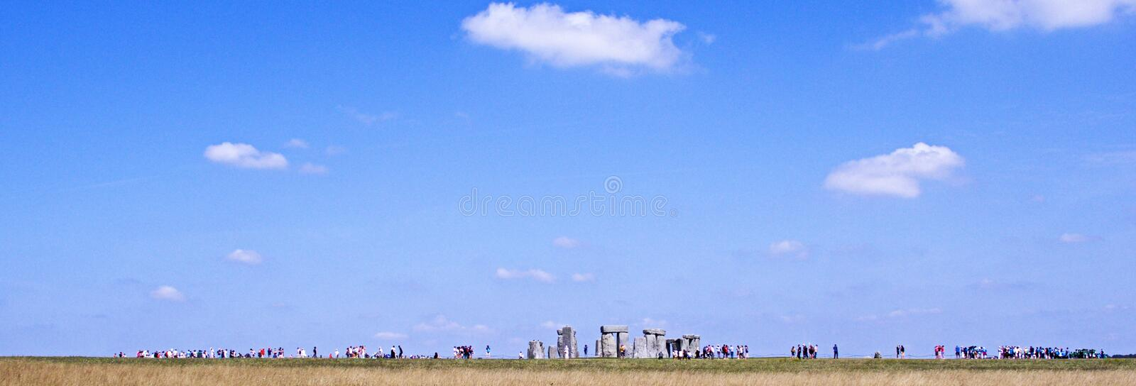 Stonehenge on a summers day with distant unrecognisable people people viewing the stones. royalty free stock image