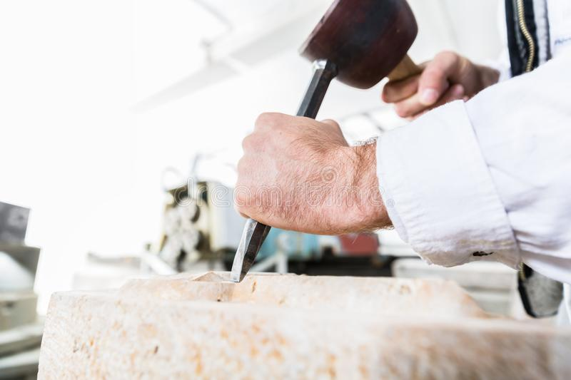 Stonemason cutting boulder with hammer and chisel royalty free stock photos