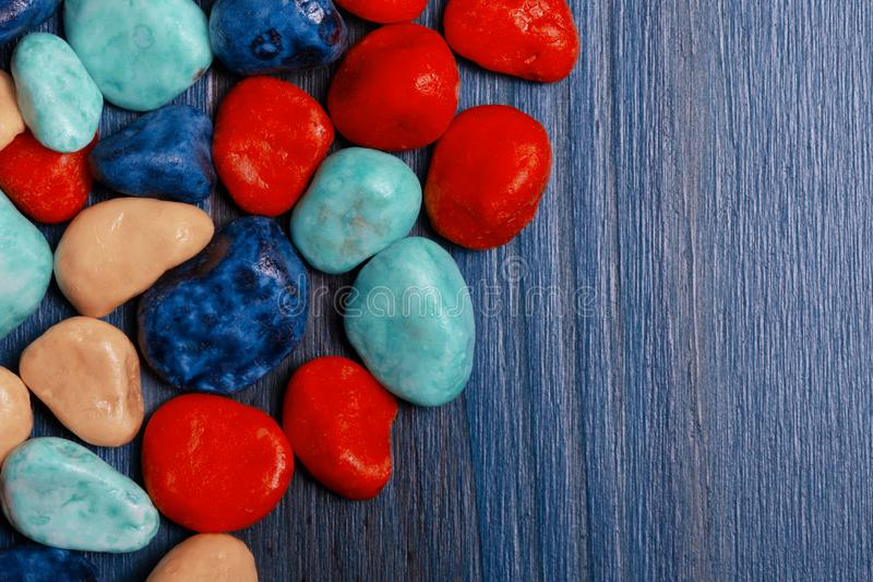 Stones of assorted colors on blue background royalty free stock image