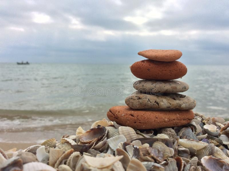 Stones balance pebbles stack on the beach. Pebbles stack on the beach, sea and boat, coast of the Azov Sea stock photo