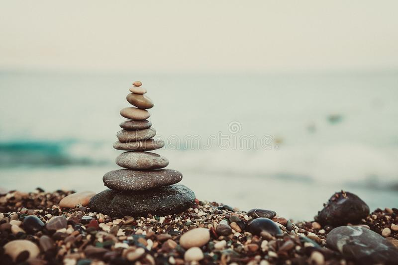 Stones balance and wellness retro spa concept. Close-up pyramid from stones stack over sea. cinematic toning. Stones balance and wellness retro spa concept royalty free stock photo