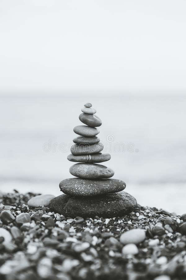 Stones balance and wellness retro spa concept. Close-up pyramid from stones stack over sea. Black and white. Stones balance and wellness retro spa concept royalty free stock image
