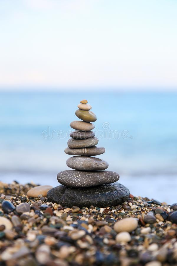 Stones balance and wellness retro spa concept. Close-up pyramid from stones stack over sea. Clear color. Stones balance and wellness retro spa concept royalty free stock image