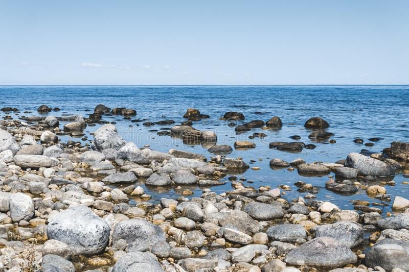 Stones and blue water stock image