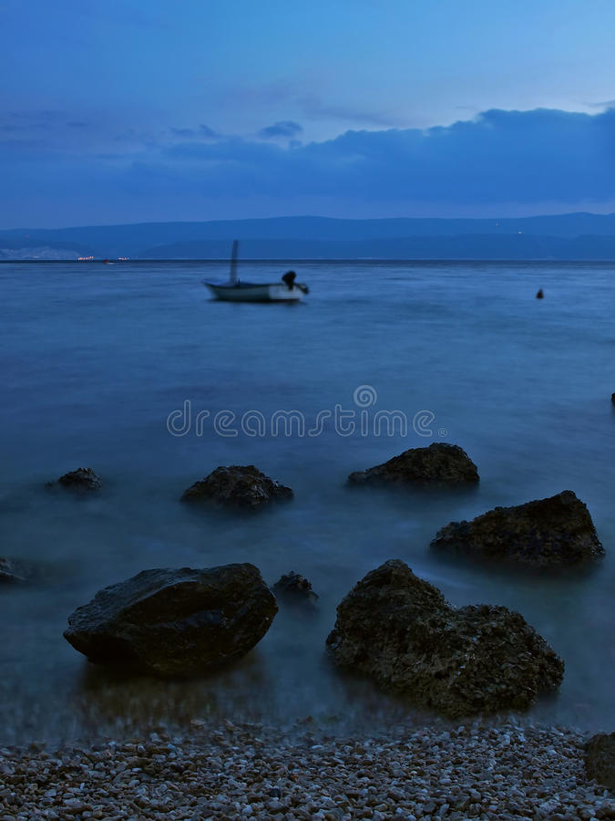 Stones and boat at misty sea stock image