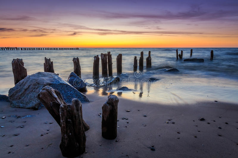 Stones and breakwater at sunset. In Niechorze, Poland. Long exposure photography royalty free stock images