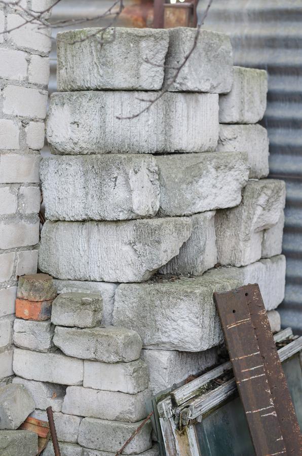 Stones, bricks and foam blocks are stacked. A group of used building materials outdoors. Without people. The vertical arrangement of the photo royalty free stock photography