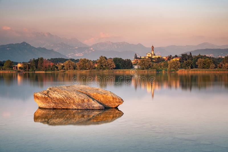 Stones in calm lake. With a typical lombardy church in the background, Lake of Pusiano, Italy stock photo