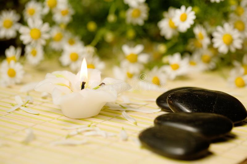 Stones and candle. A candle and stones for spa massage stock photos