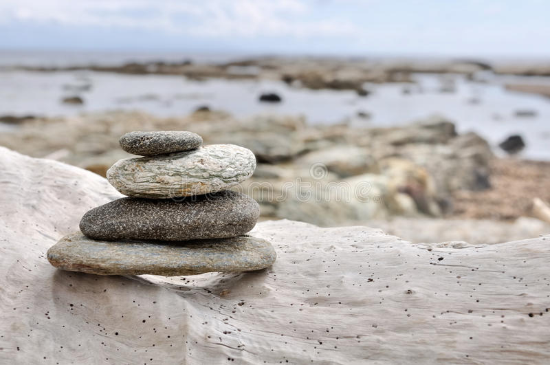 Stones on driftwood. Pebbles piled on driftwood on the seafront royalty free stock images