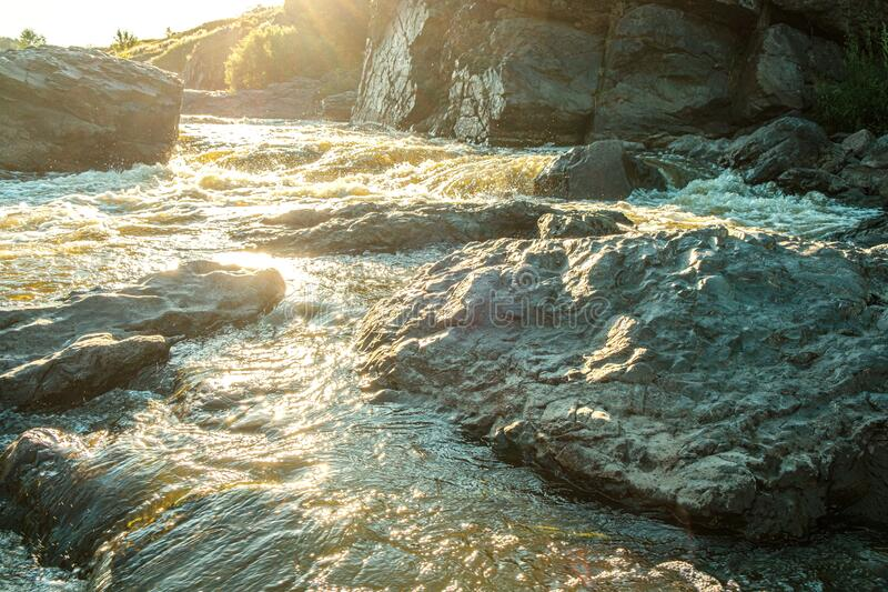 Among the stones the fast streams of a mountain river from behind bright sun shines royalty free stock photos