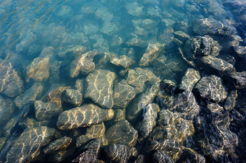 Stones with gleams of sunshine under clear water. royalty free stock photos