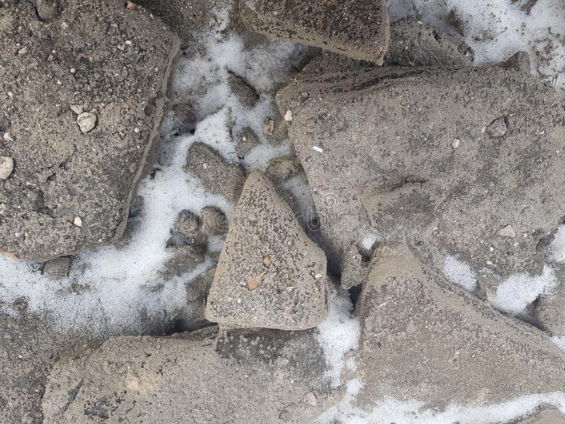 Stones of granite on snow background texture, snowy stones near mountains river, snow-covered land royalty free stock photos
