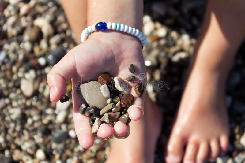 Stones in the hand of the little boy sitting on the beach stock photo