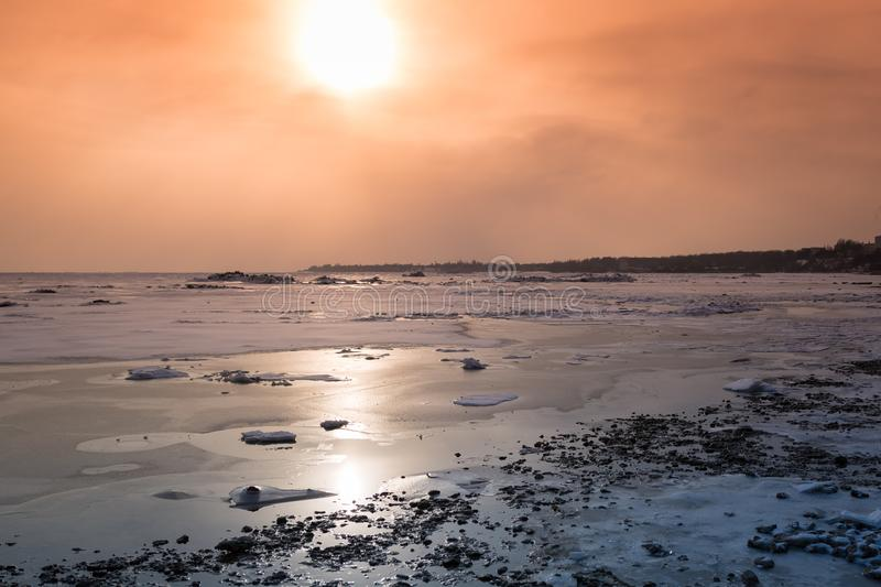 Stones, ice floes and a frozen sea in the sun`s rays at sunset. Tinted winter landscape royalty free stock photo