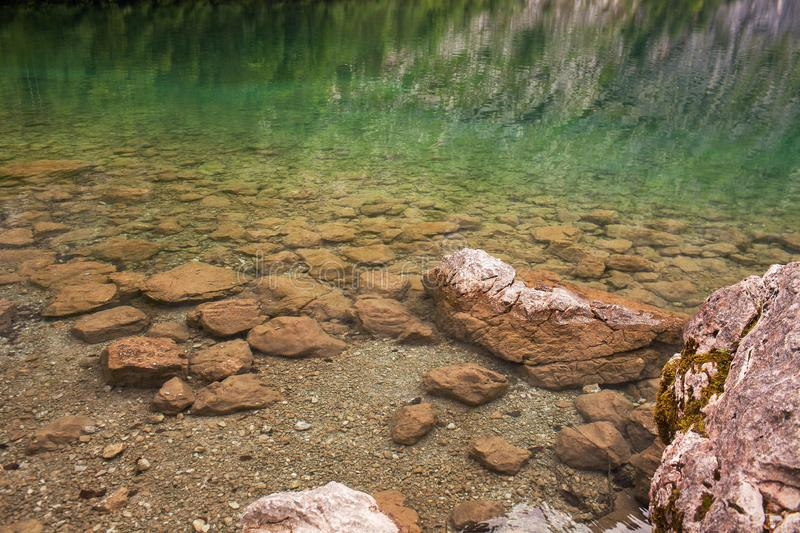 Stones lie in a crystal clear lake in the Alps.  royalty free stock image