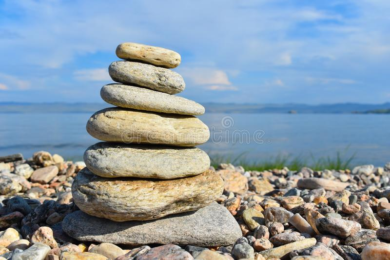 Stones meditation figures. Symbolical statue of several stones. Tradition to collect  stones in private. Beautiful water landscape stock images