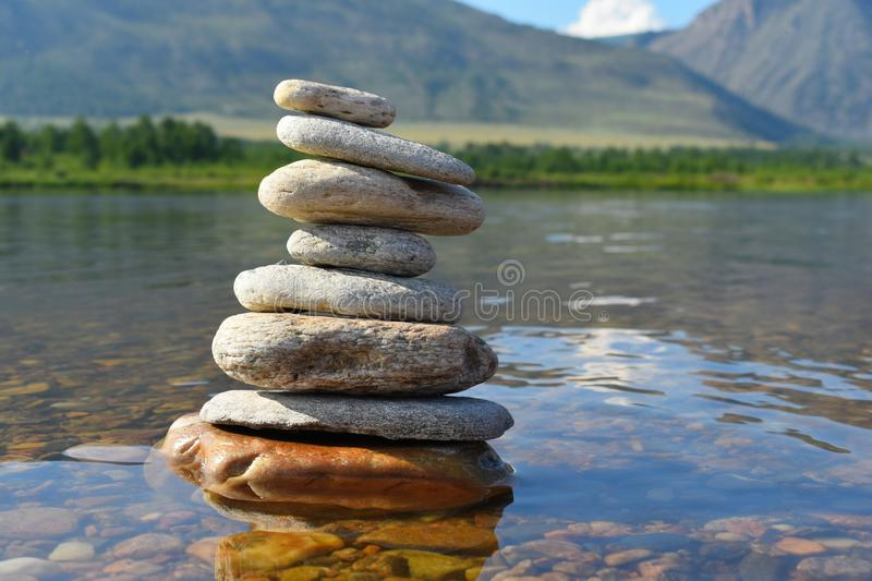 Stones meditation figures. Symbolical statue of several stones. Tradition to collect  stones in private. Beautiful water landscape royalty free stock photo