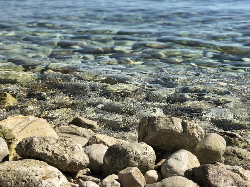 Stones pebbles rocks in blue sea royalty free stock photo
