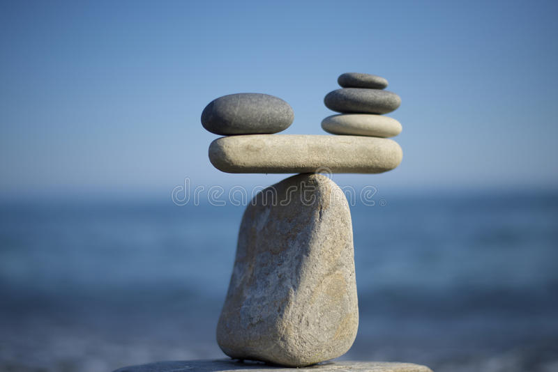 Stones pile background. Scales balance. Balanced stones on the top of boulder. Decide problem. To weight pros and cons. Balance of stones on a blue sky stock images