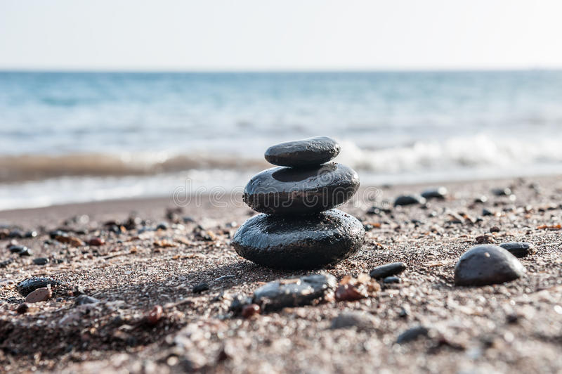 Stones pyramid on the beach, sea in the background. Zen and harmony. Small depth of field royalty free stock image