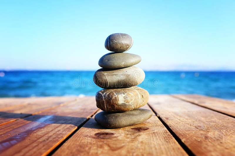 Stones pyramid on over beach wooden deck symbolizing harmony, zen and balance.  royalty free stock photos