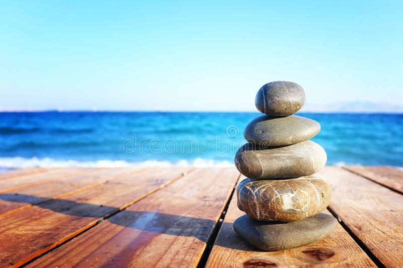 Stones pyramid on over beach wooden deck symbolizing harmony, zen and balance.  royalty free stock images
