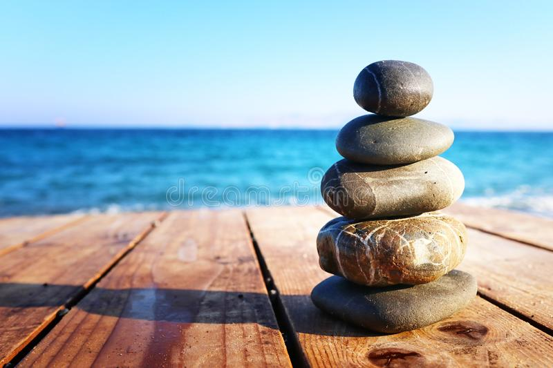 Stones pyramid on over beach wooden deck symbolizing harmony, zen and balance.  stock photos