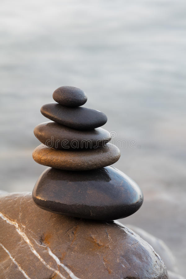 Stones pyramid on pebble beach symbolizing stability, harmony, balance. Shallow depth of field stock images