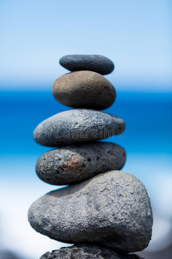 Concept of harmony and balance. Rock Zen on a background of rock. Stones pyramid on pebble beach symbolizing stability, zen, harmony, balance. Shallow depth of royalty free stock photography